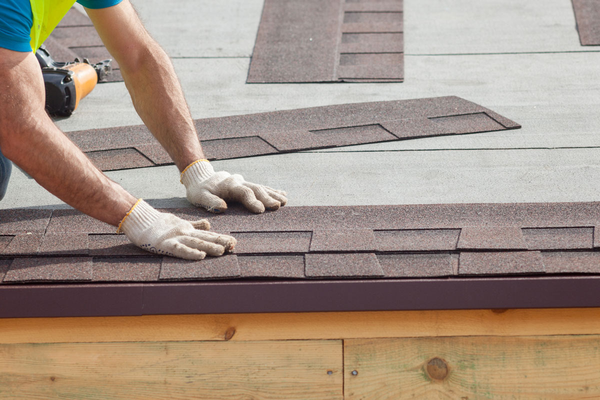 Man repairing and replacing roof shingles on a house roof